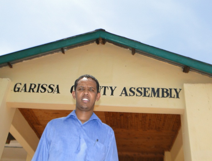 "A young Kenyan man stands in front of a building labeled ""Garissa County Assembly."""