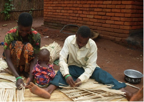 Photo of Malawian woman and man weaving baskets together