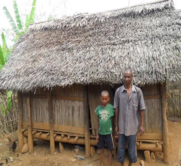 Rasolo and his son stand in front of their old home.
