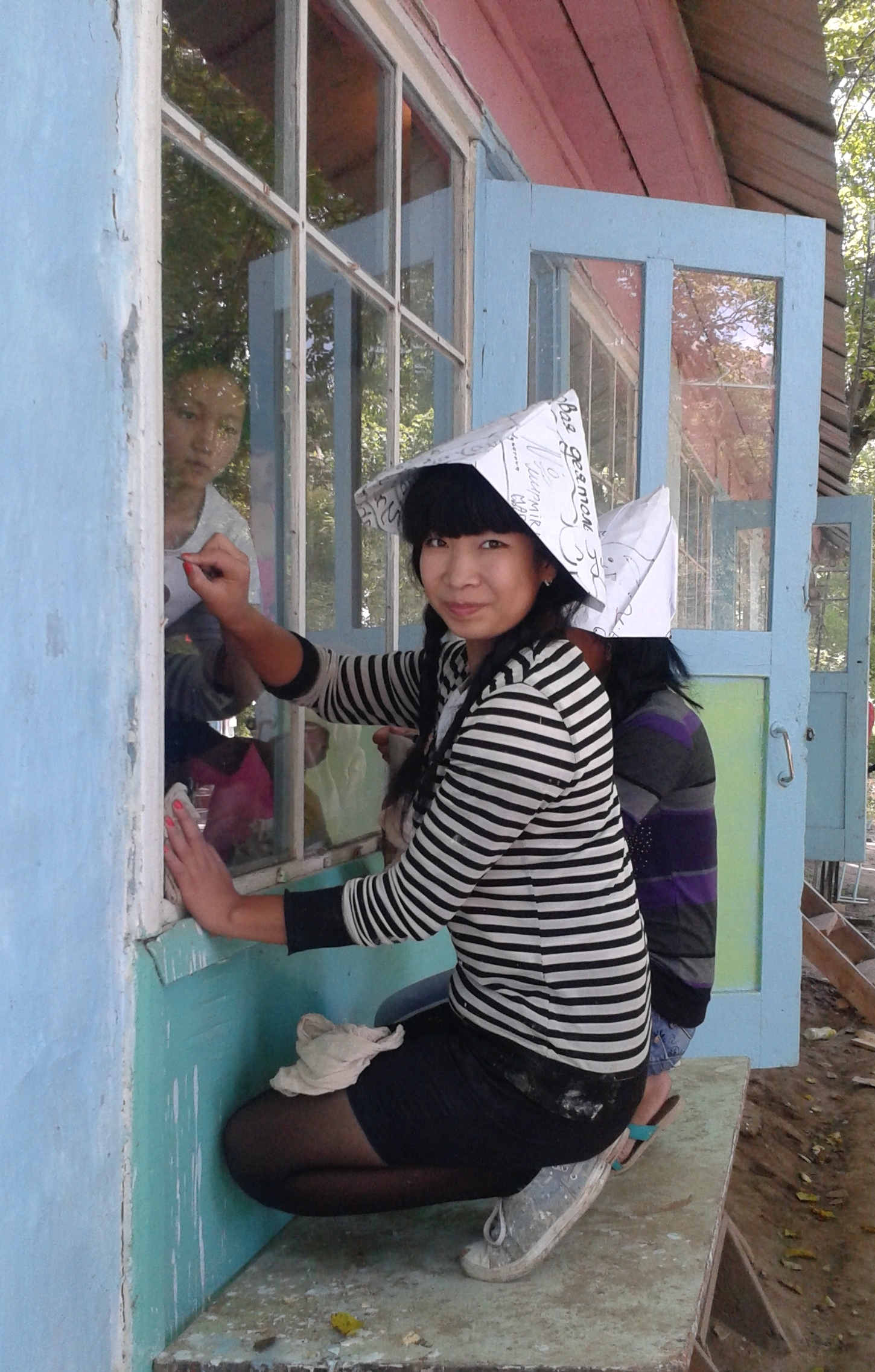 Adina, with other volunteers, repairs and reconstructs summer camp cottages at a  residential institution for young orphans.