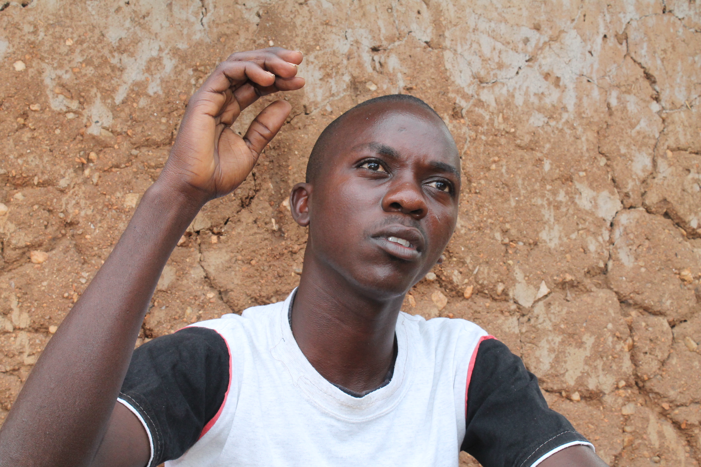 A young Kenyan man sitting in front of a wall