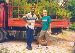 Partners Farmer to Farmer volunteer Norman Bezona and local coordinator Benito Jasmin transport bamboo plants in northern Haiti.