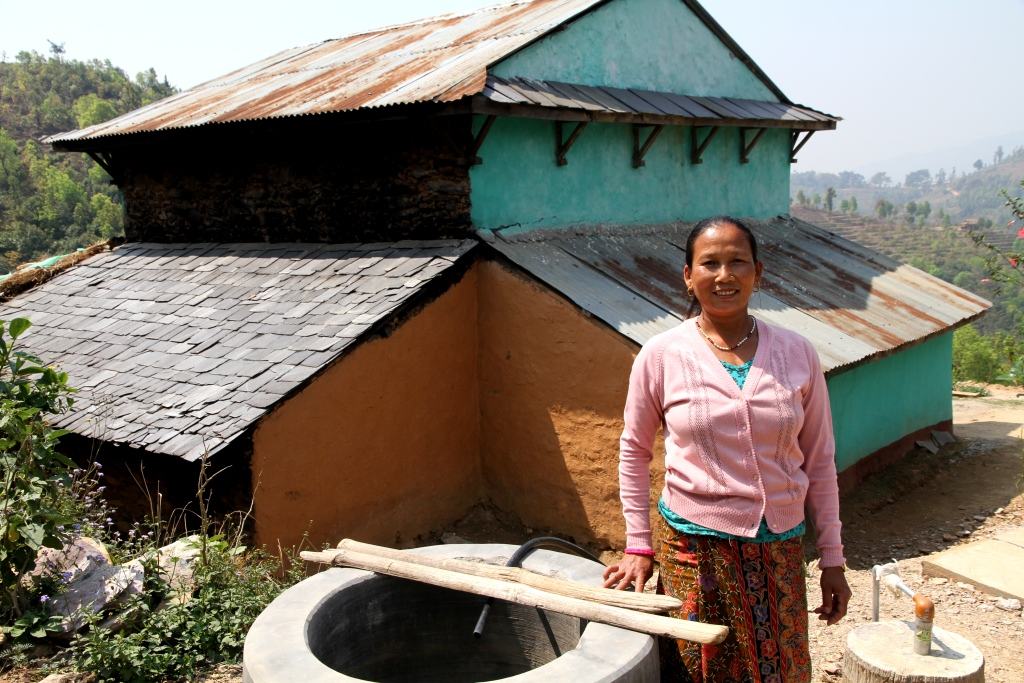 A woman stands next to a waste pit, installed with biogas technology, in front of her home.