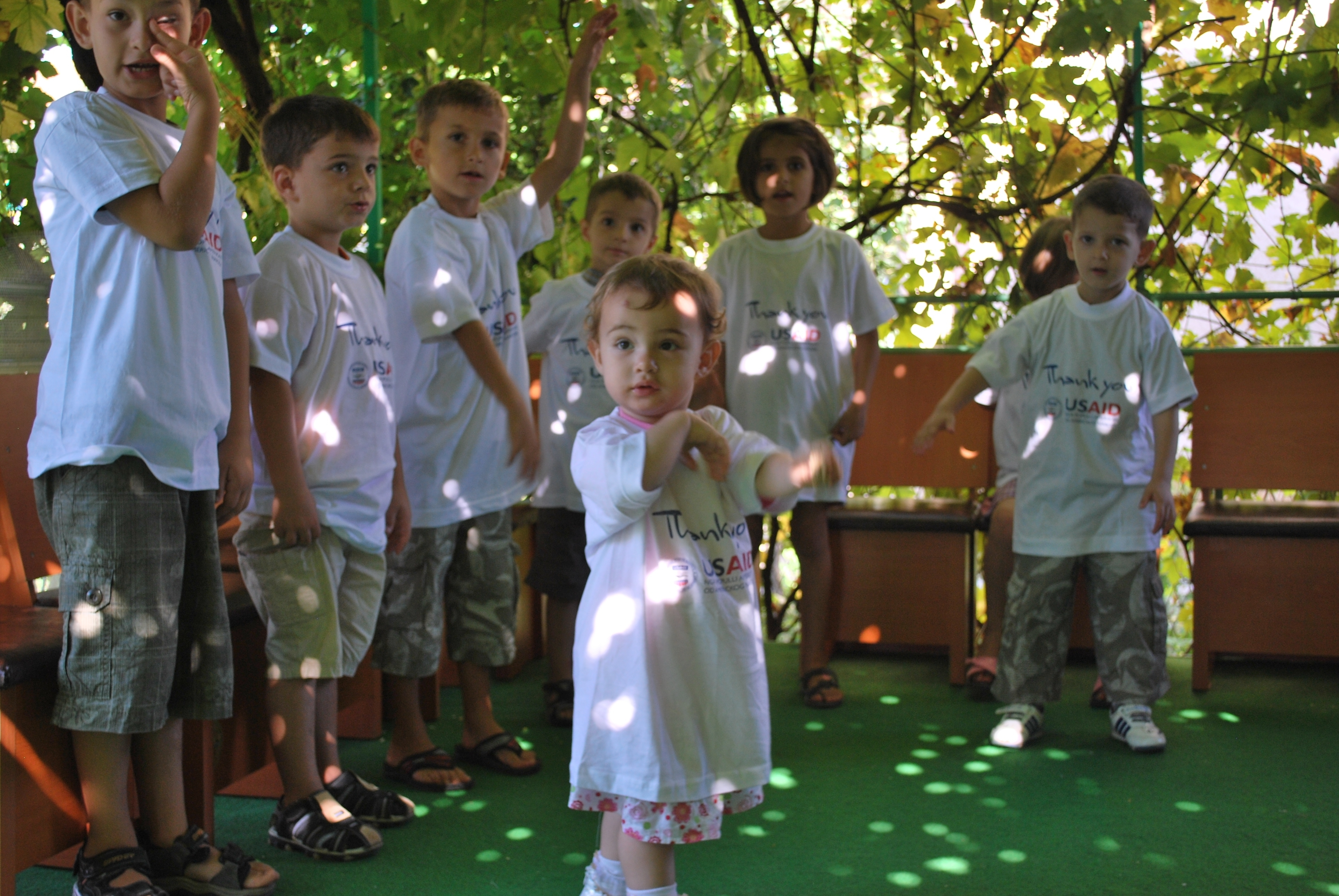 Children at the BAMBI daycare center playing in the garden during a USAID staff visit.
