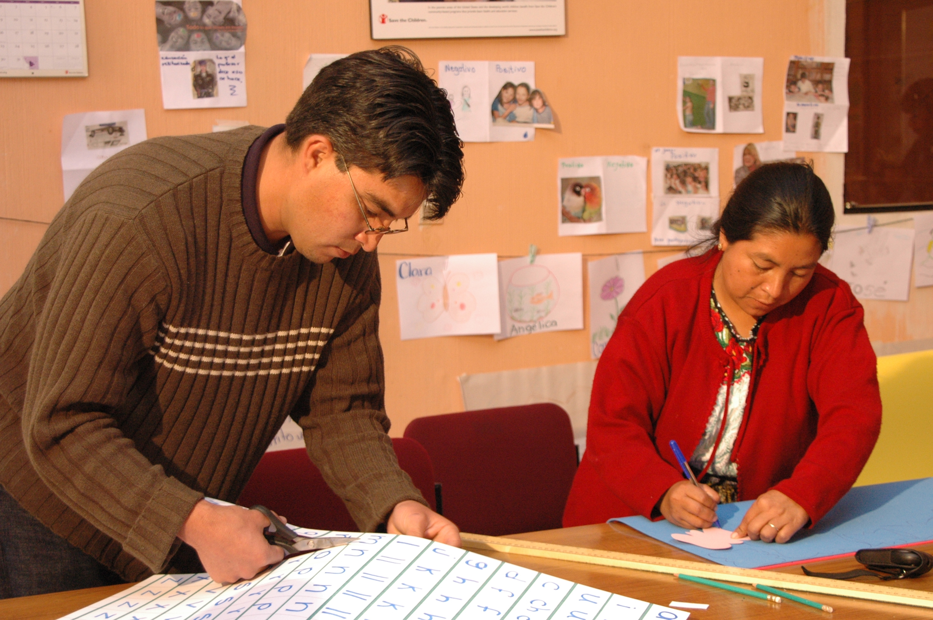 A man and woman work on the production of a domestic violence publication