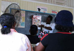 A healthcare professional giving a presentation at a prevention of mother to child transmission group education session.