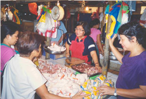 Stall owner Angelina Bulos at the Muntinlupa Market is pleased that both vendors and customers now have a cleaner market thanks