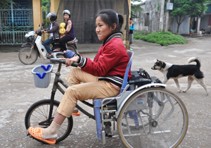 Pham Thi Bich Ngoc rides the modifi ed wheelchair to get her out into the community.