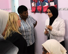 Hana Masoud briefs USAID representatives on how Burqa residents have improved access to health care services in their village.