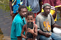 A boy holding a mangrove poses for the camera while standing in front of residents of his village